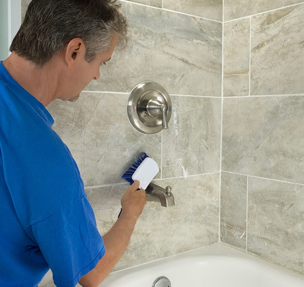 Worker shown cleaning tile in bathroom
