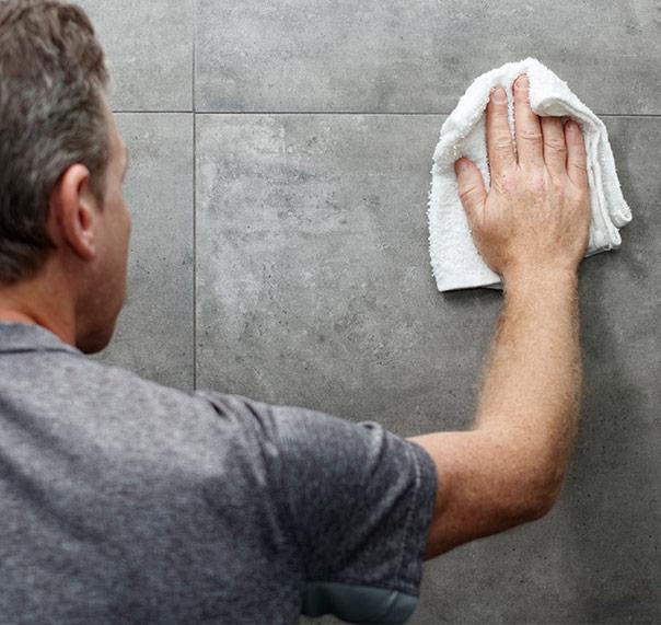 Man cleaning dark tile in bathroom